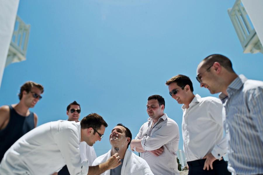 groomsman shaving the groom in mykonos wedding