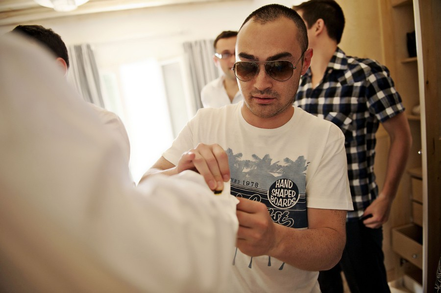 groomsman helping the groom on a wedding in mykonos