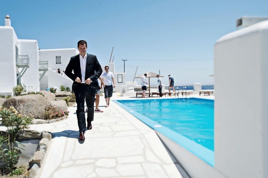 groom walking to the ceremony in mykonos wedding