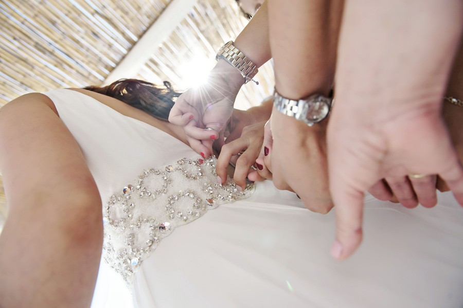 bridesmaids helping the bride with the wedding dress in mykonos saint George