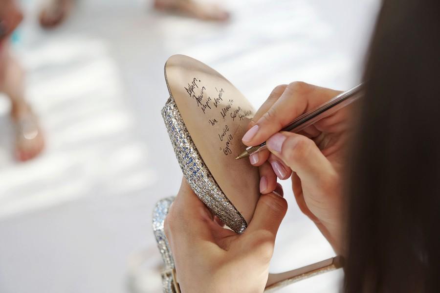 bride holding the jimmy Choo bridal shoe in mykonos