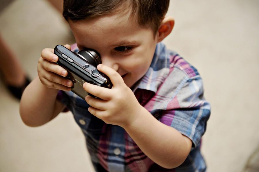 a boy holds a camera in mykonos wedding