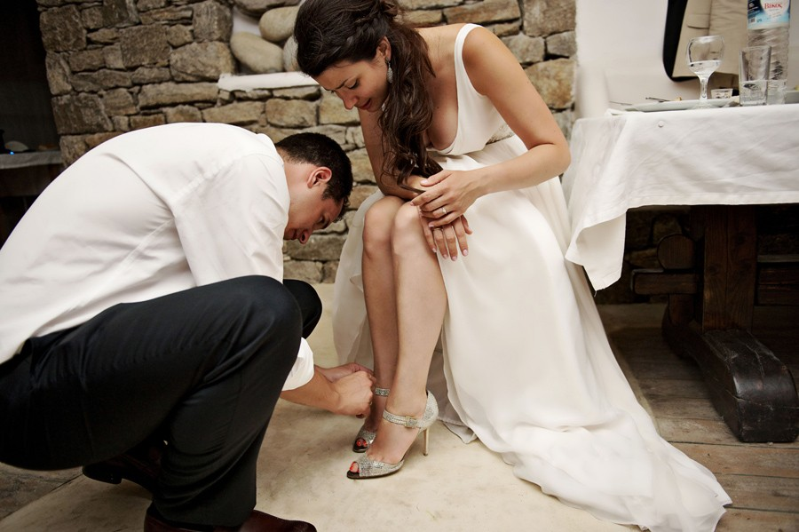 groom helping the bride with her shoes in mykonos wedding