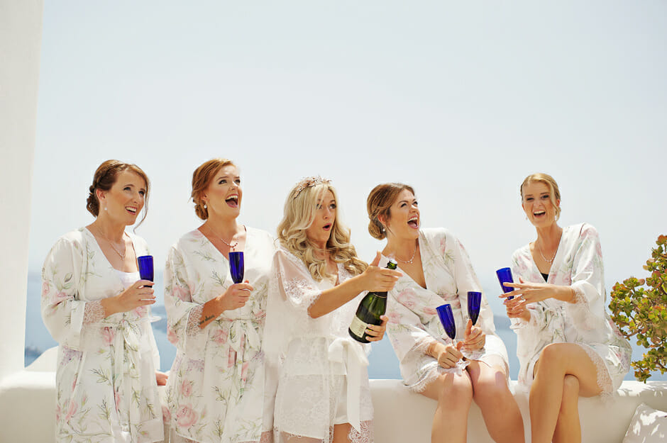 bride with bridesmaids open champagne in le ciel santorini wedding