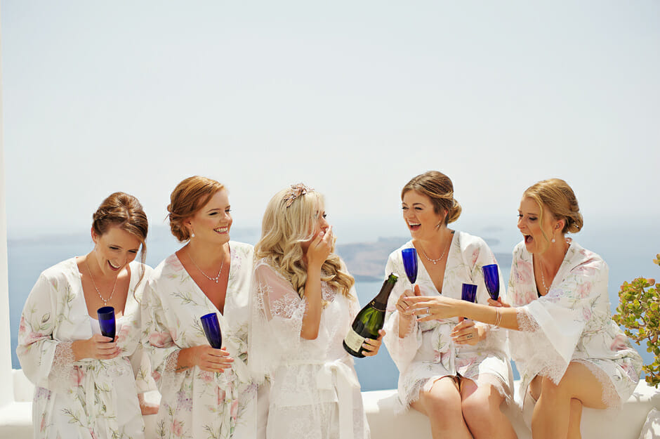 bride with bridesmaids drinking champagne in le ciel santorini wedding