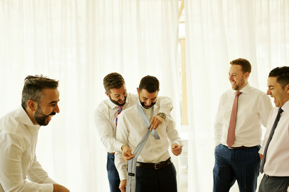 brother of the groom helping with the tie
