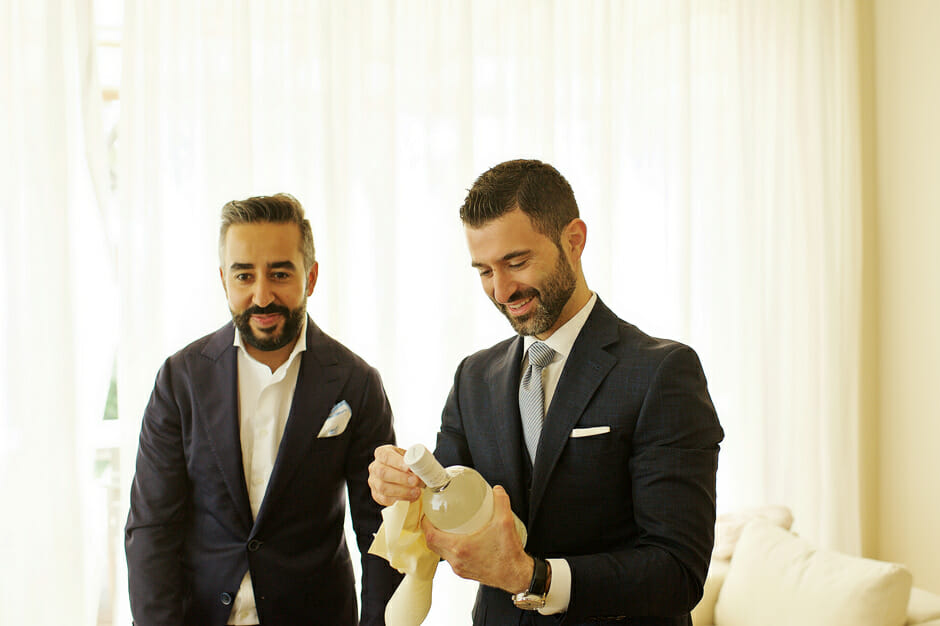 groom opens champagne before the wedding in athens riviera