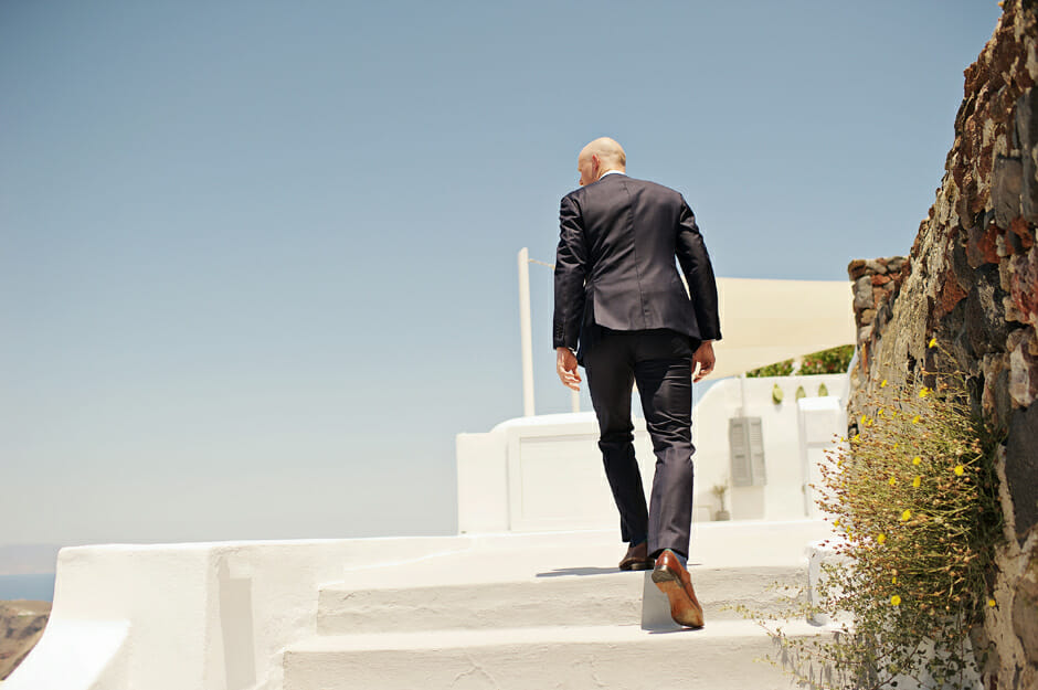 groom walking up the stairs for the elopement ceremony in santorini