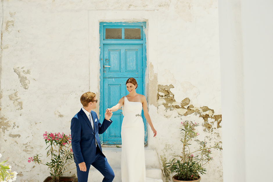 bride and groom in front of a blue door in greek islands