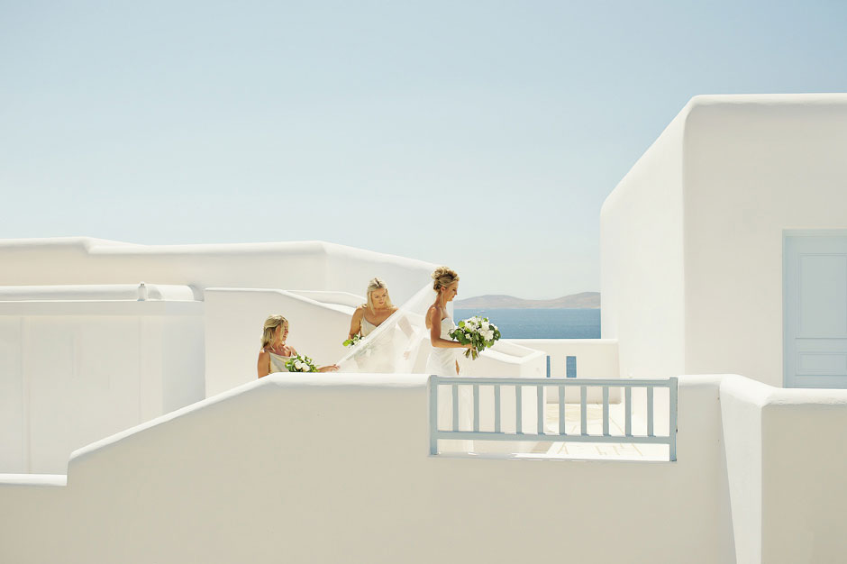 bridesmaids helping the bride with the wedding dress in mykonos wedding