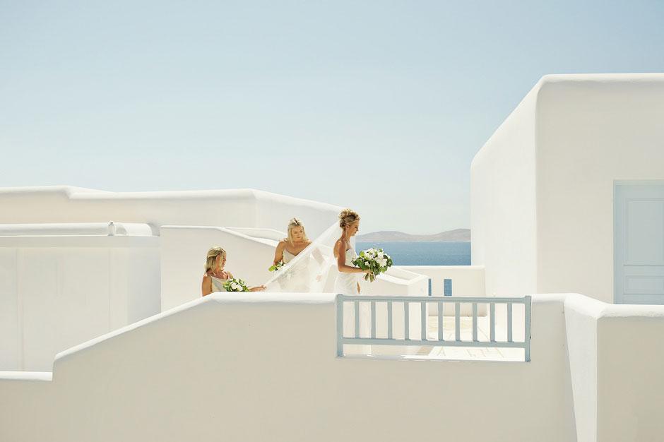 bridesmaids helping the bride with the wedding dress in mykonos wedding