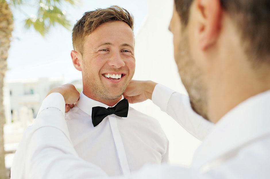 groom helps groomsman in mykonos wedding