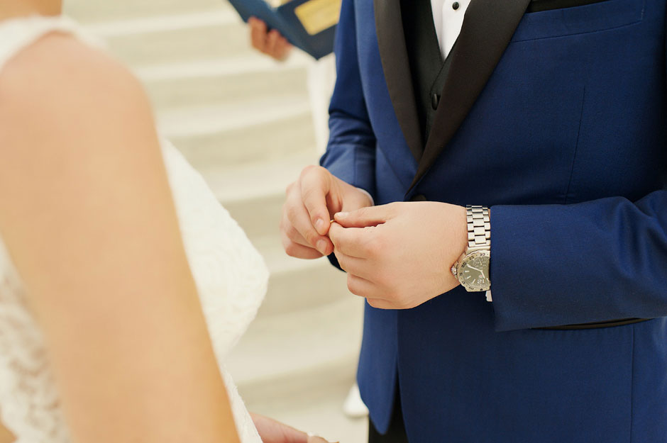 groom-holding-the-wedding-ring-on-their-elopement-day-in-santorini-santa-irene-wedding-venue-