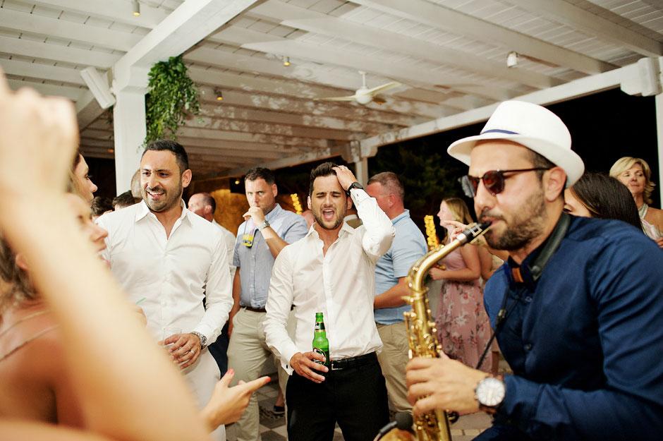 groom sings on his wedding party in mykonos