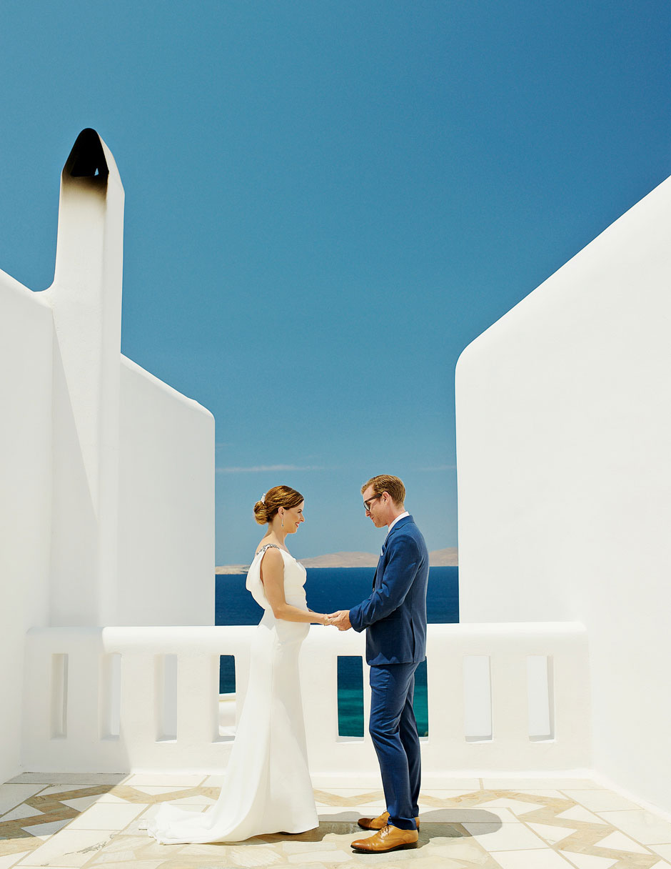 groom with blue suit anf bride with white wedding dress in mykonos