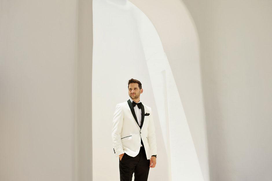 groom with white tuxedo in mykonos wedding