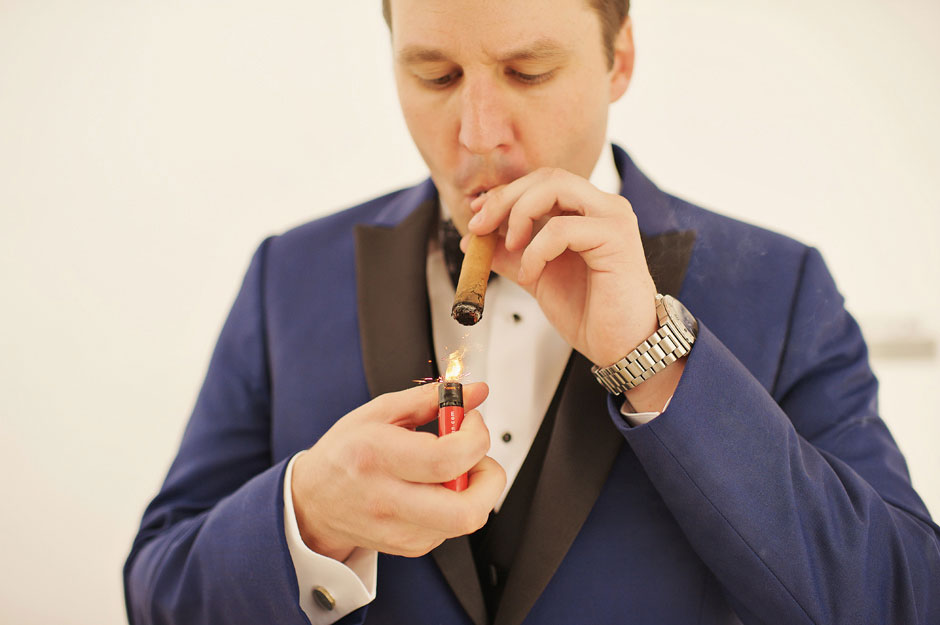 groom-with-blue-tuxedo-lights-up-a-havana-cigar-before-the-elopement-in-santorini