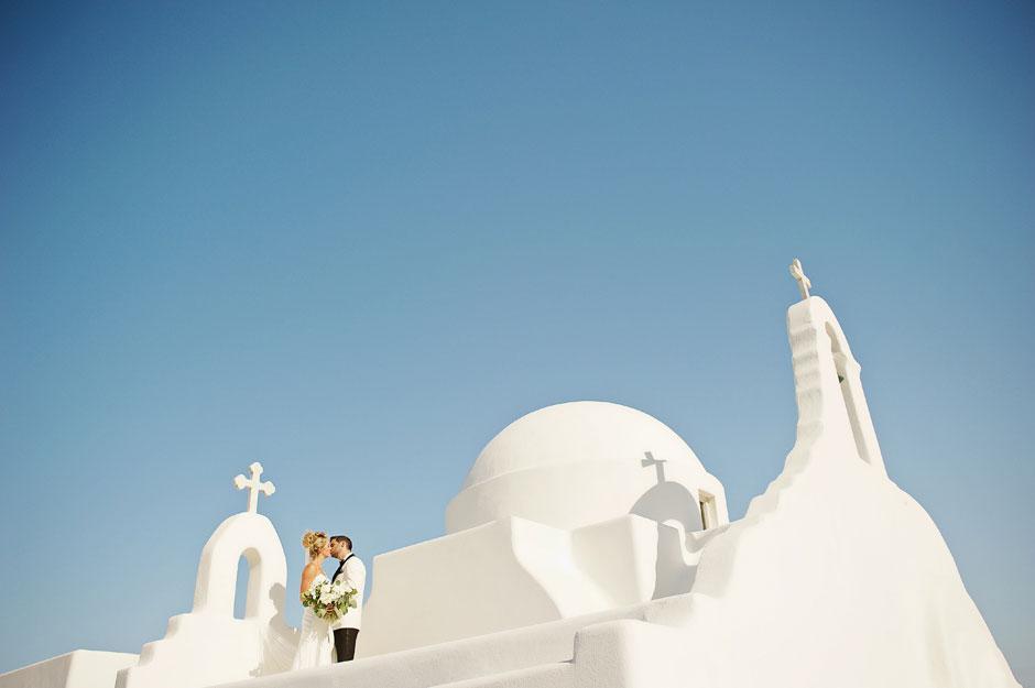 wedding couple in mykonos white chapel rooftop